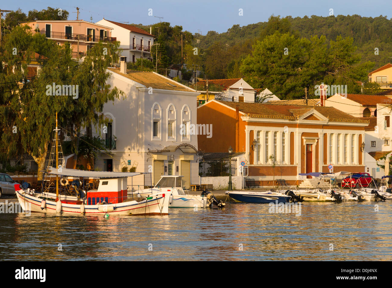 Fishing boat moored in front of classical buildings at Gaios harbour Paxos, Greece - Stock Image