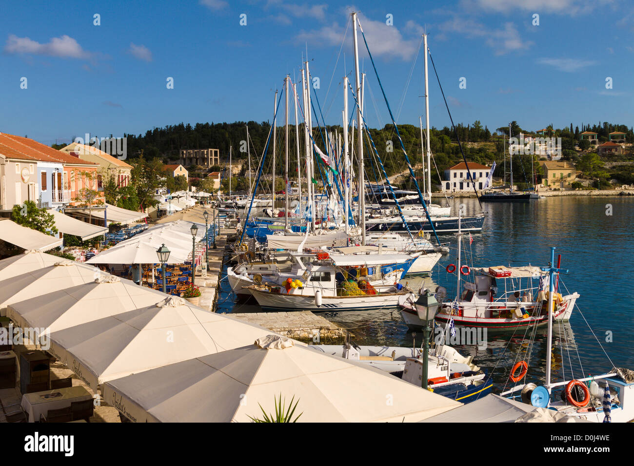 Boats moored in front of tavernas at Fiscardo, Kefalonia, Greece - Stock Image