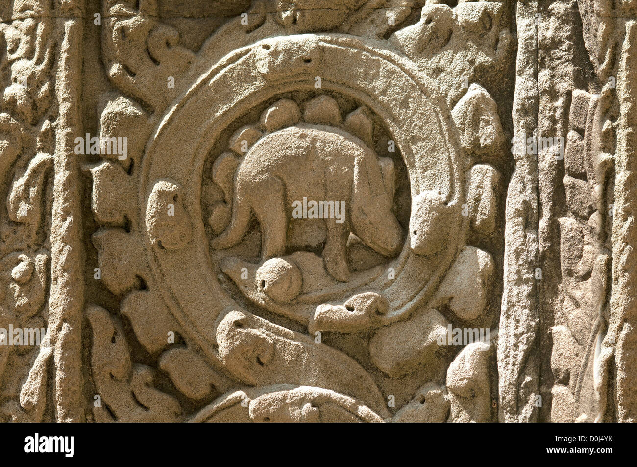 stone carving of an animal ressembling a stegosaurus, a rhinocereus or chameleon, Ta Prohm, Jungle temple, Angkor, - Stock Image