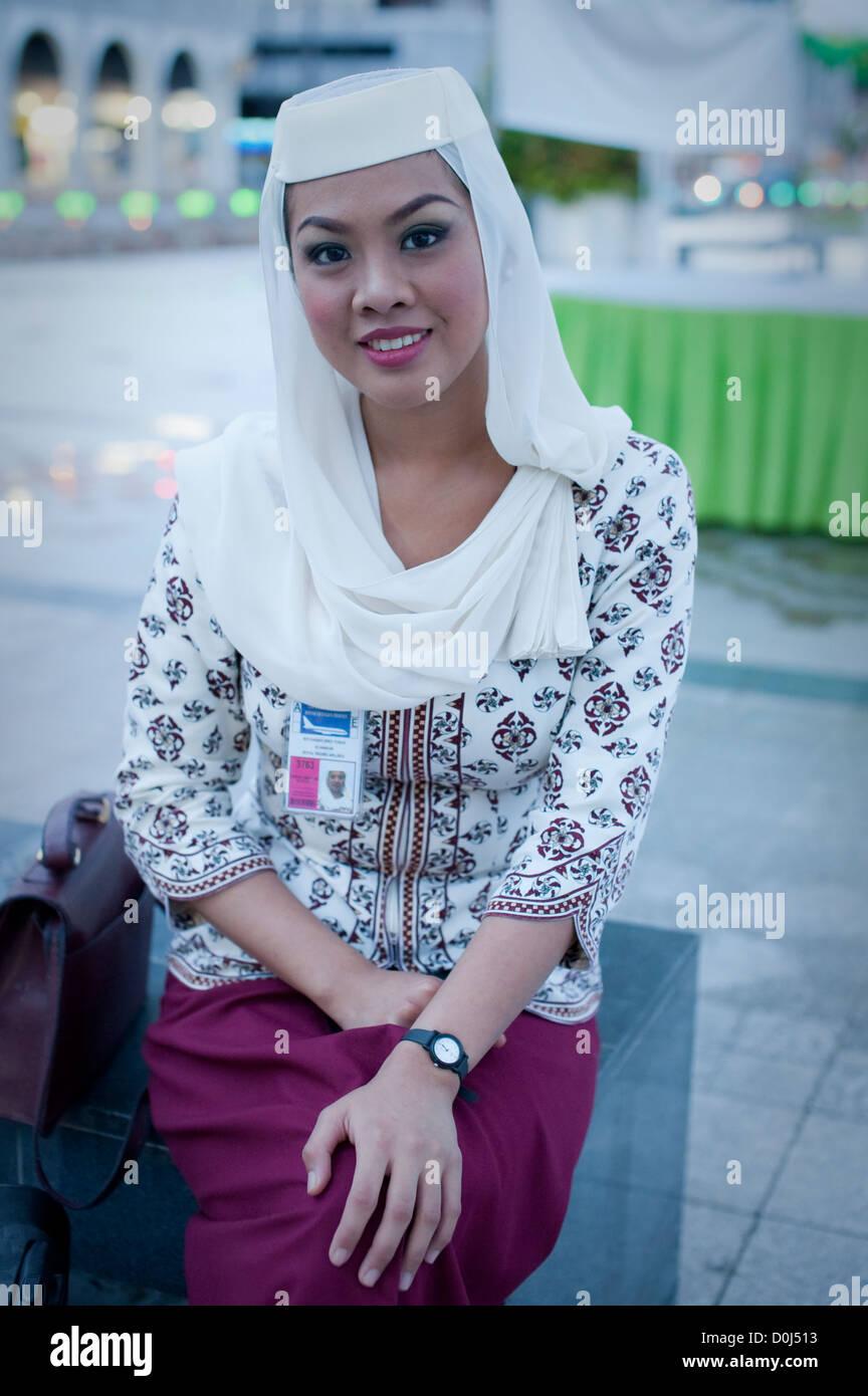 Royal Brunei Airlines flight attendant waits for her lift, Brunei - Stock Image
