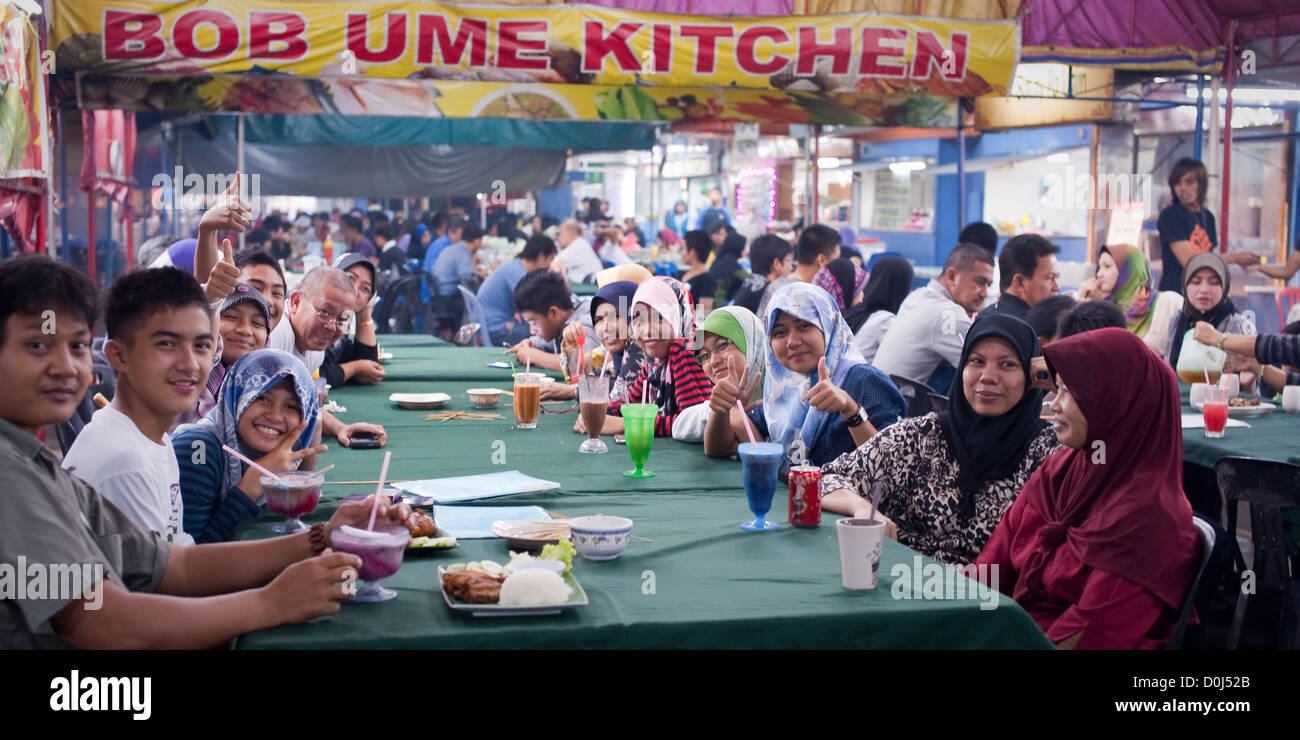 Local people enjoy drinks and a meal at a long table in a food court, Brunei - Stock Image