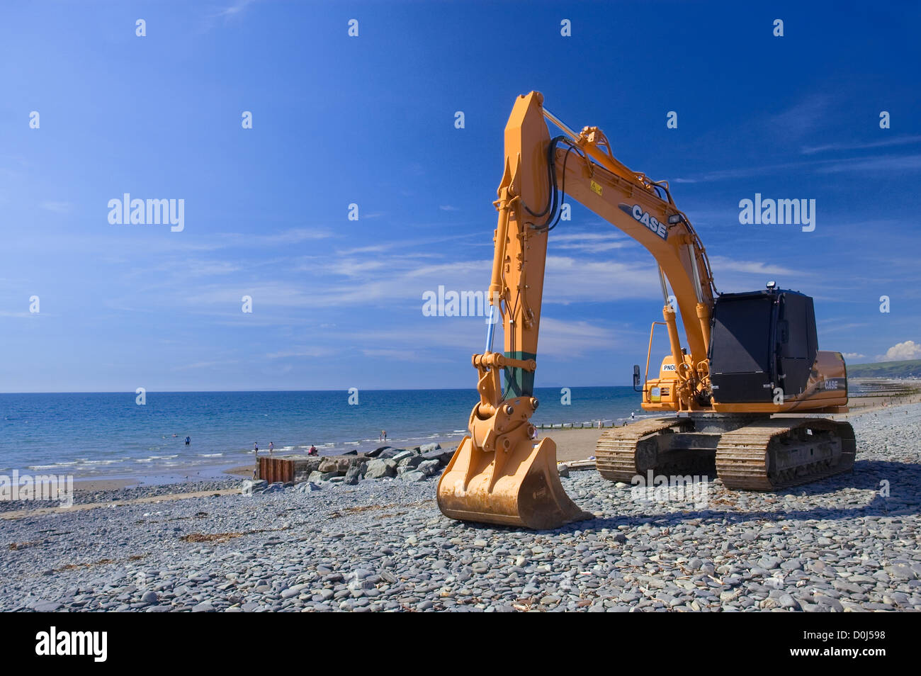 A mechanical digger on the beach at Borth. - Stock Image