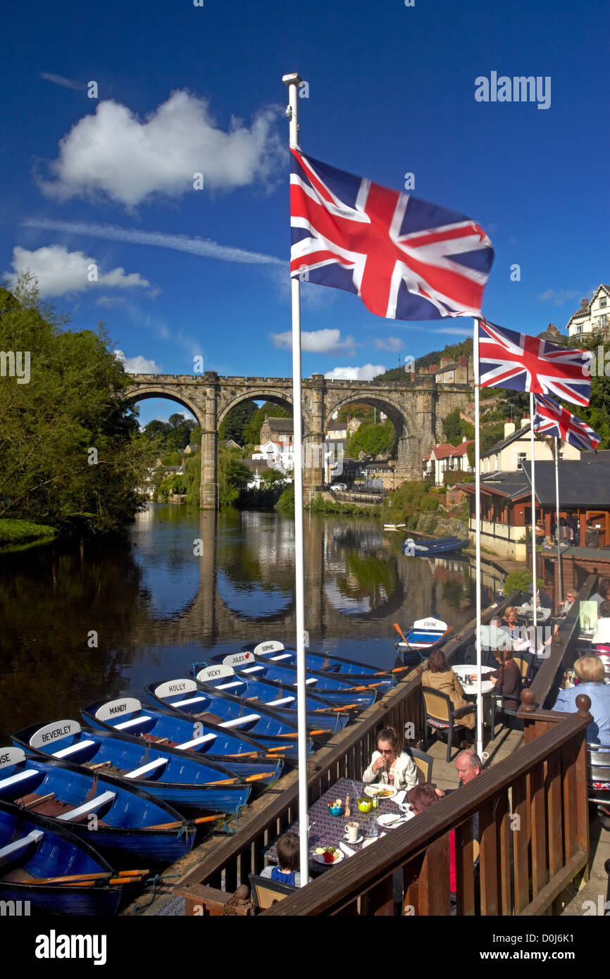 A view of the River Nidd from the riverside cafe with the Victorian railway viaduct reflected in the waters below. - Stock Image