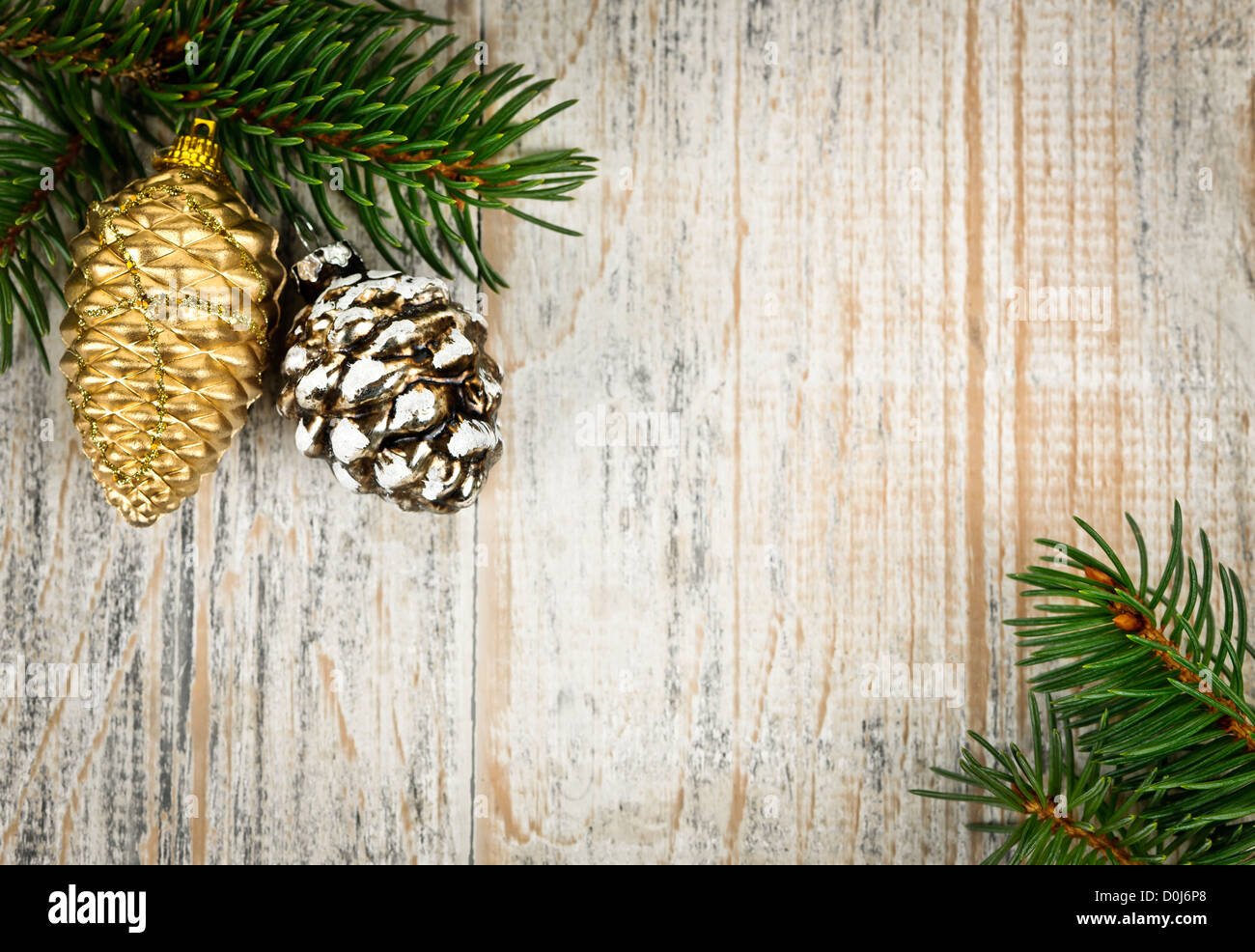 Christmas golden balls and pine cone on spruce branch with wooden background - Stock Image