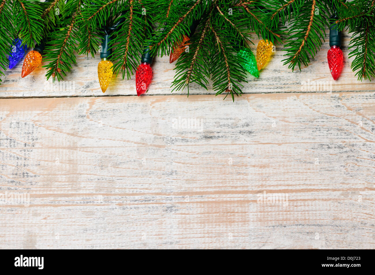 Multicolored Christmas lights on spruce branch with wooden background - Stock Image