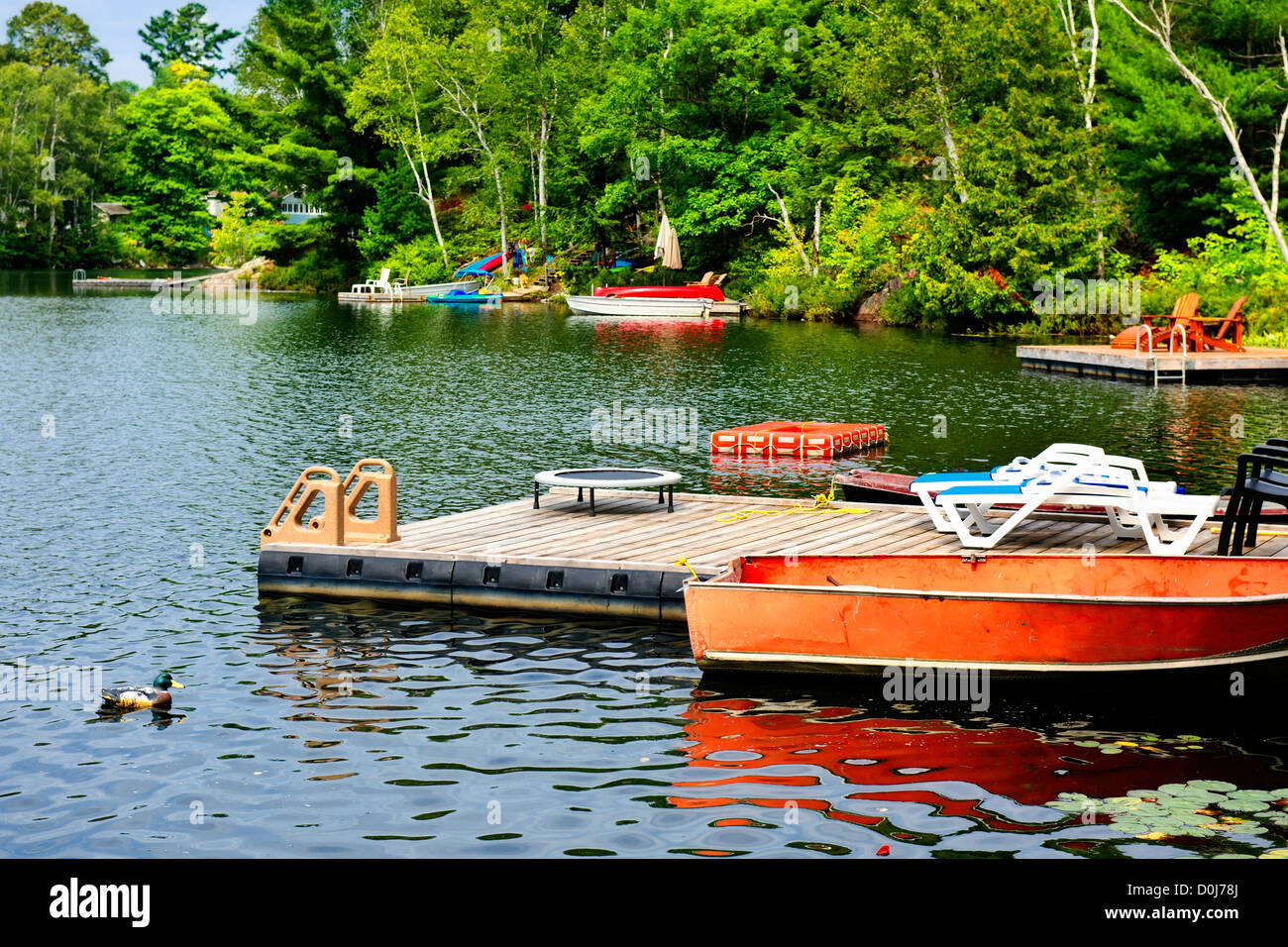 Beautiful lake with docks and diving platform in Ontario Canada cottage country - Stock Image
