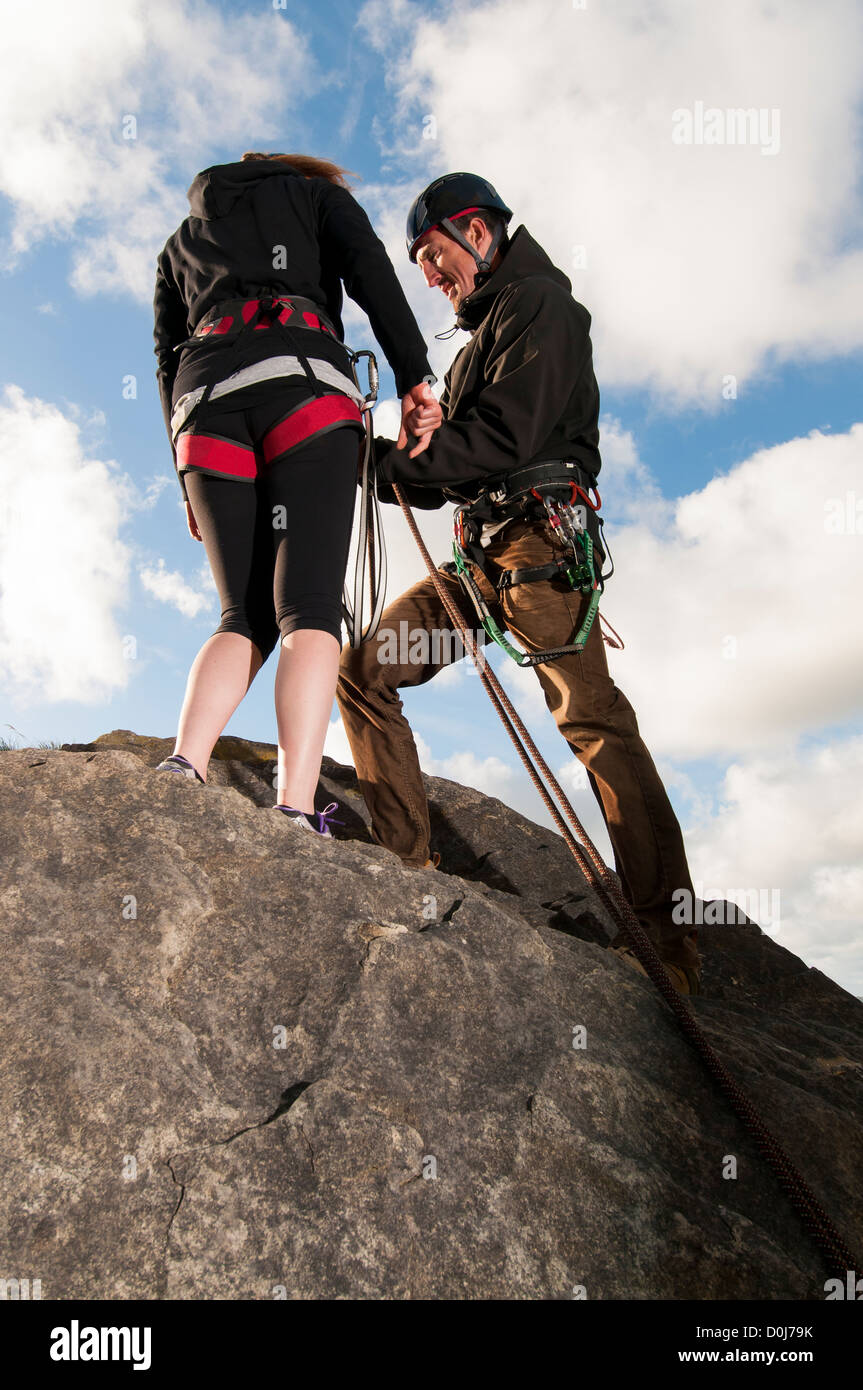 Abseiling instructor demonstrating how to clip in and fasten up, on top of rock. - Stock Image