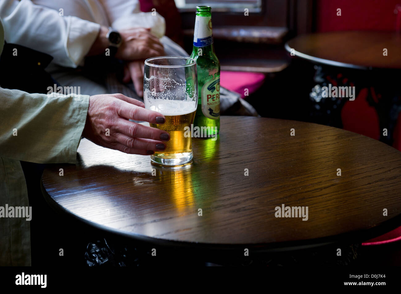 A hand reaching for a pint glass in a pub. - Stock Image