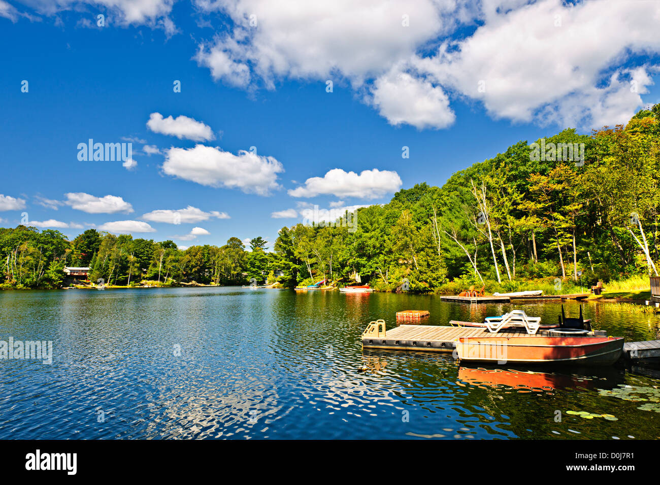 Beautiful lake with docks in Ontario Canada cottage country - Stock Image