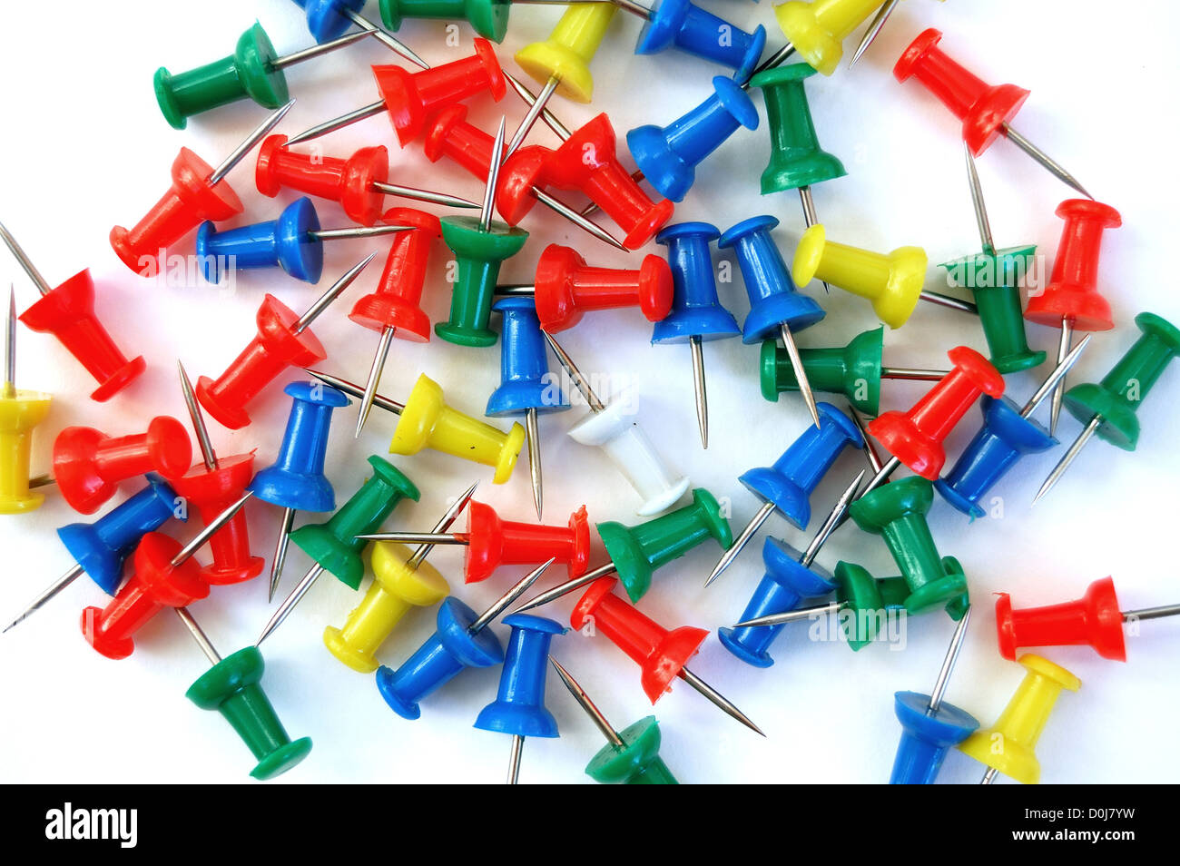 Colorful push pins on white background. - Stock Image