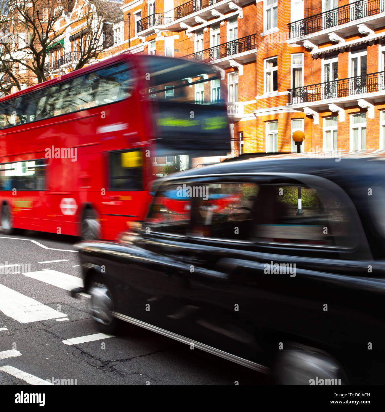 A red London bus and Black Cab Taxi approach the famous Abbey Road pedestrian crossing made famous by the cover - Stock Image