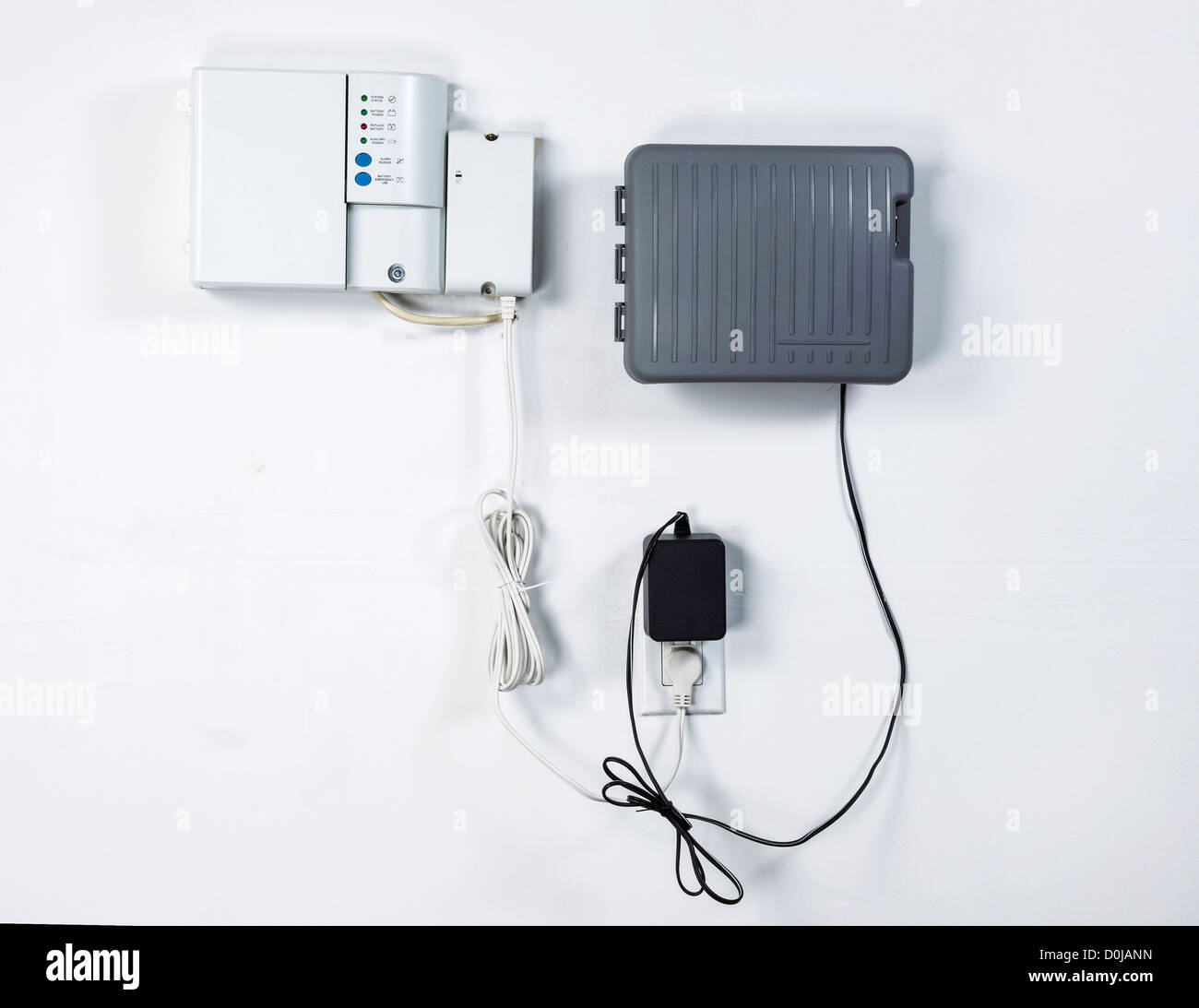 Home utilities consisting of cable and water sprinkler system with backup battery pack on garage wall - Stock Image