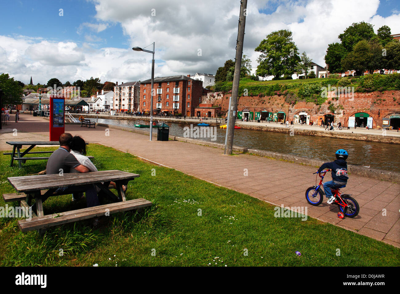 A child cycles on the towpath beside Exeter canal. - Stock Image