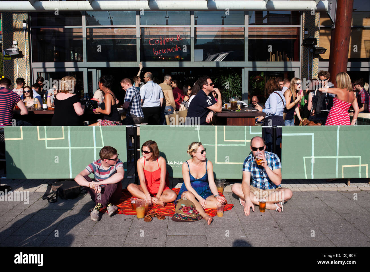 People relaxing at an Olympic torch event at Harbourside in Bristol. - Stock Image