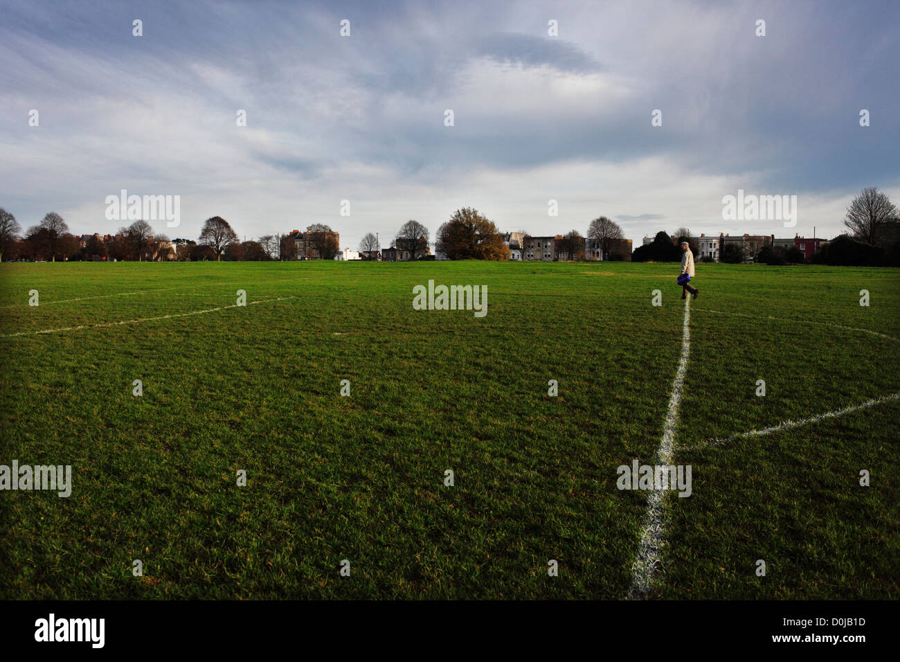 A lone man walks across a football pitch in The Downs area of Bristol. - Stock Image