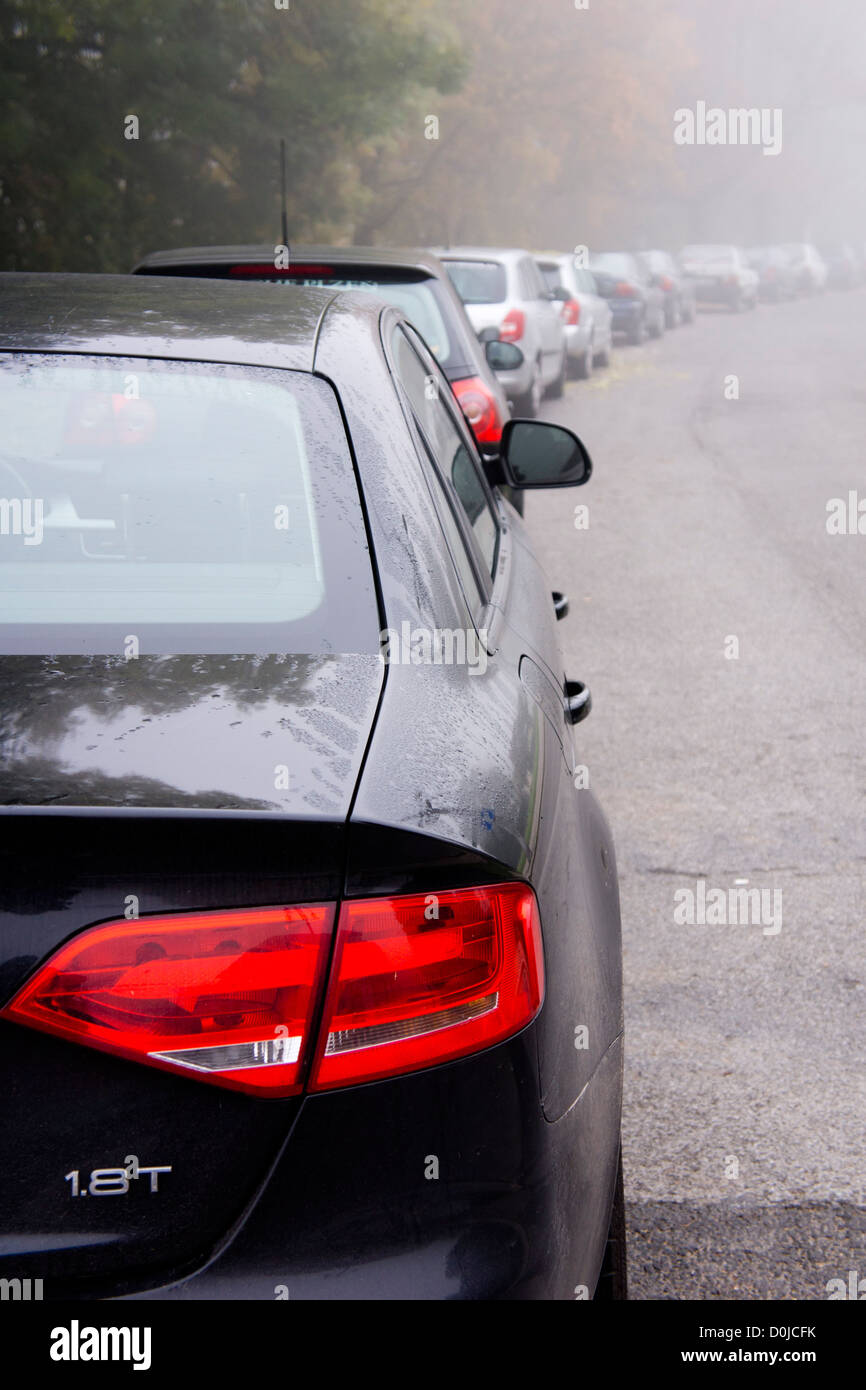 row of cars parked along a road - Stock Image