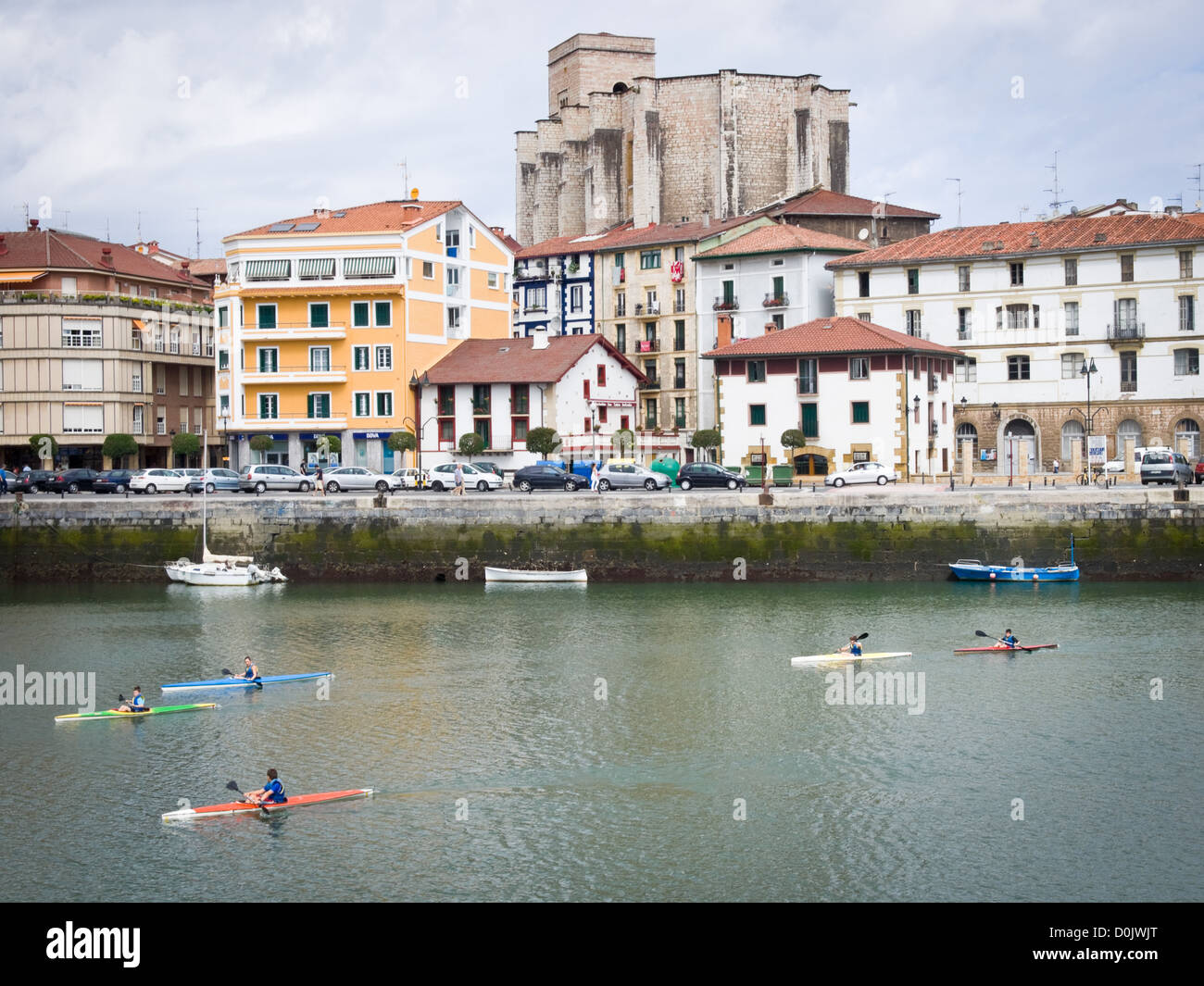 People kayaking near Zumaia, Guipuzkoa, in Northern Spain. The Basque-style Gothic church of San Pedro stands in - Stock Image