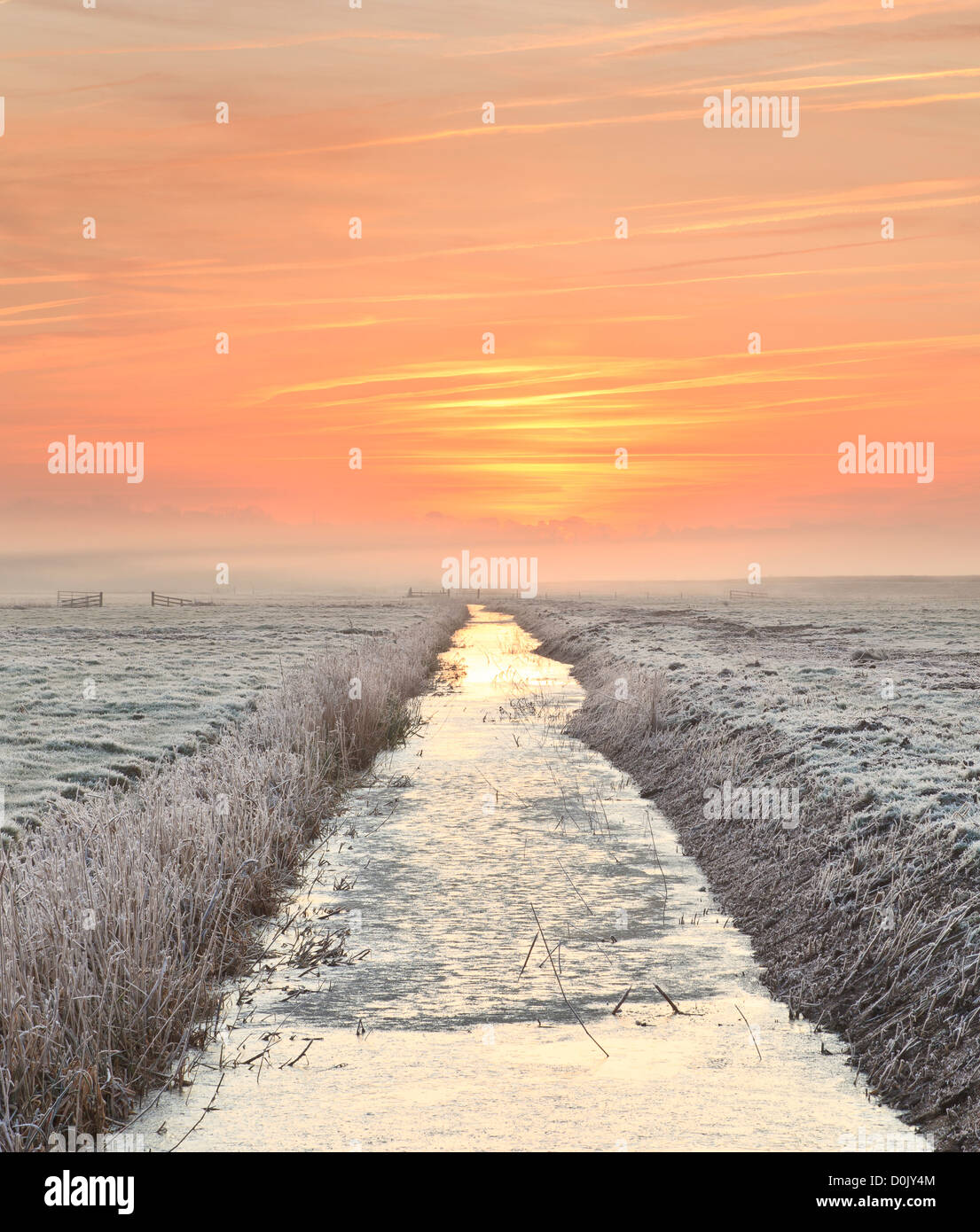 A view along a drainage channel at dawn. - Stock Image