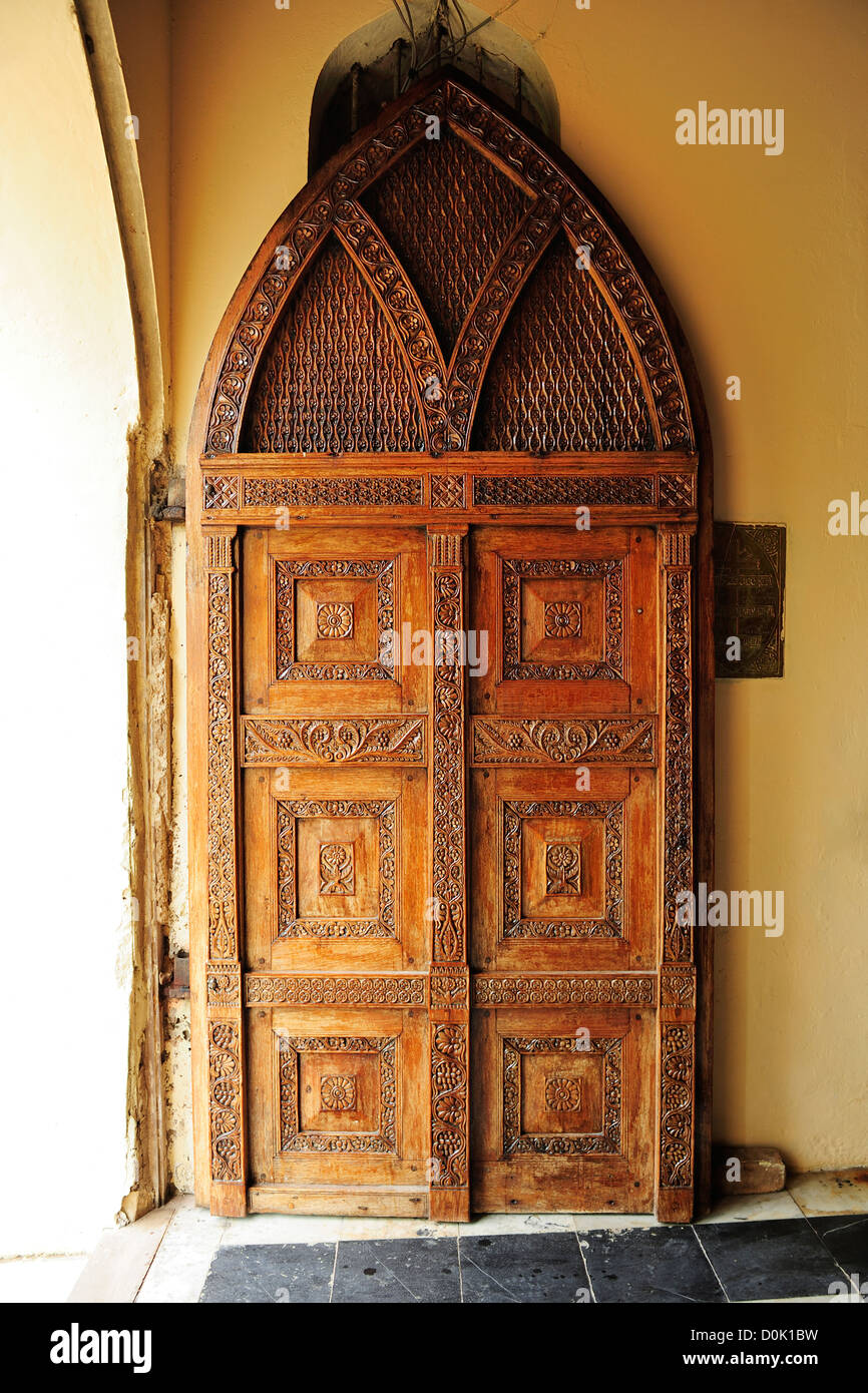 Carved wooden door at entrance to Anglican Cathedral in Stone Town, Zanzibar, Tanzania, East Africa - Stock Image