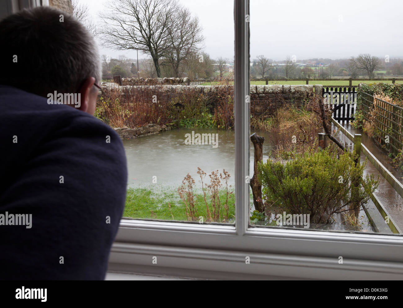 Concerned householder looking out of the window at rising flood water in their garden, County Durham, England UK - Stock Image