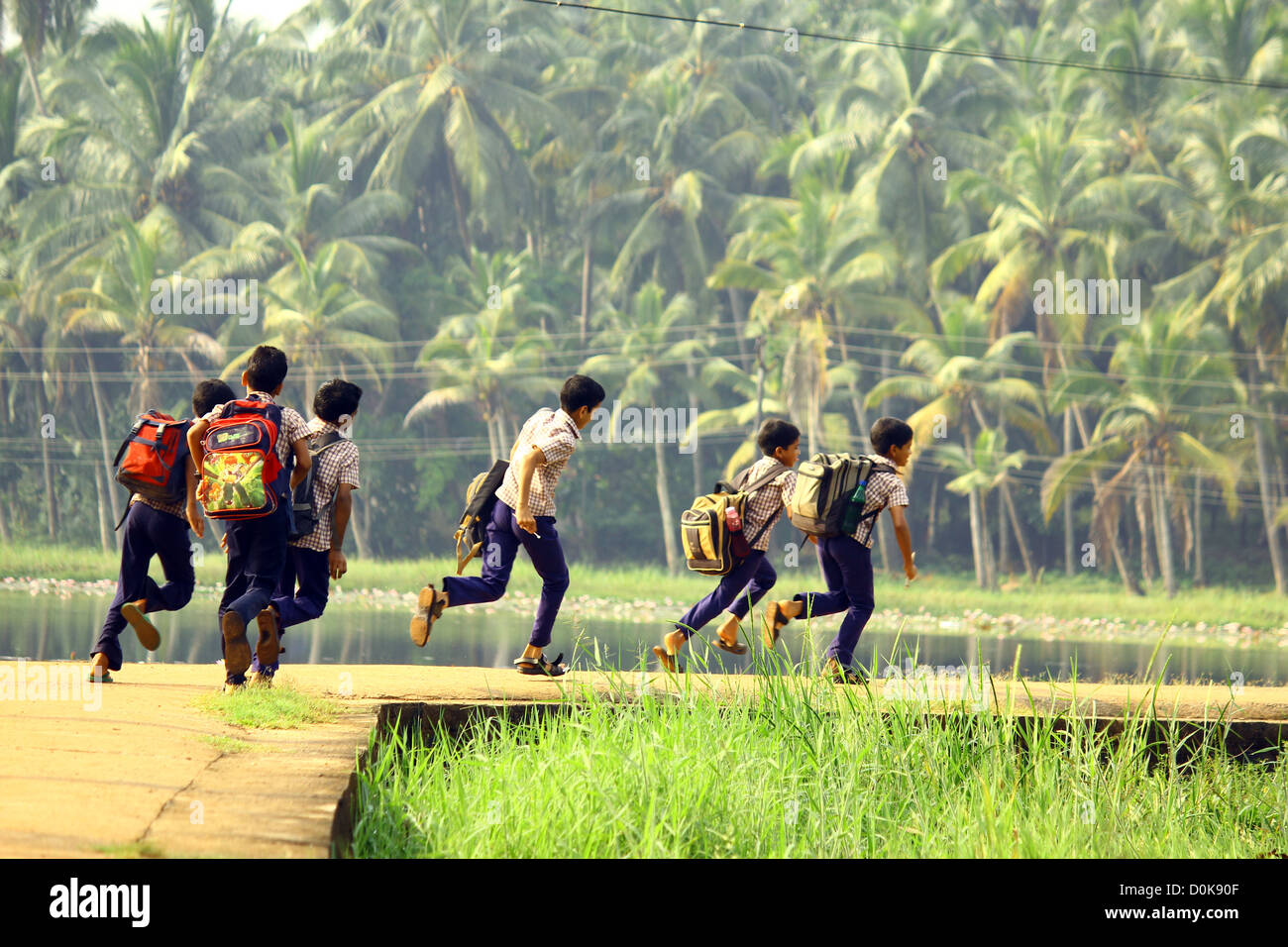 School children running to school in rural kerala - Stock Image