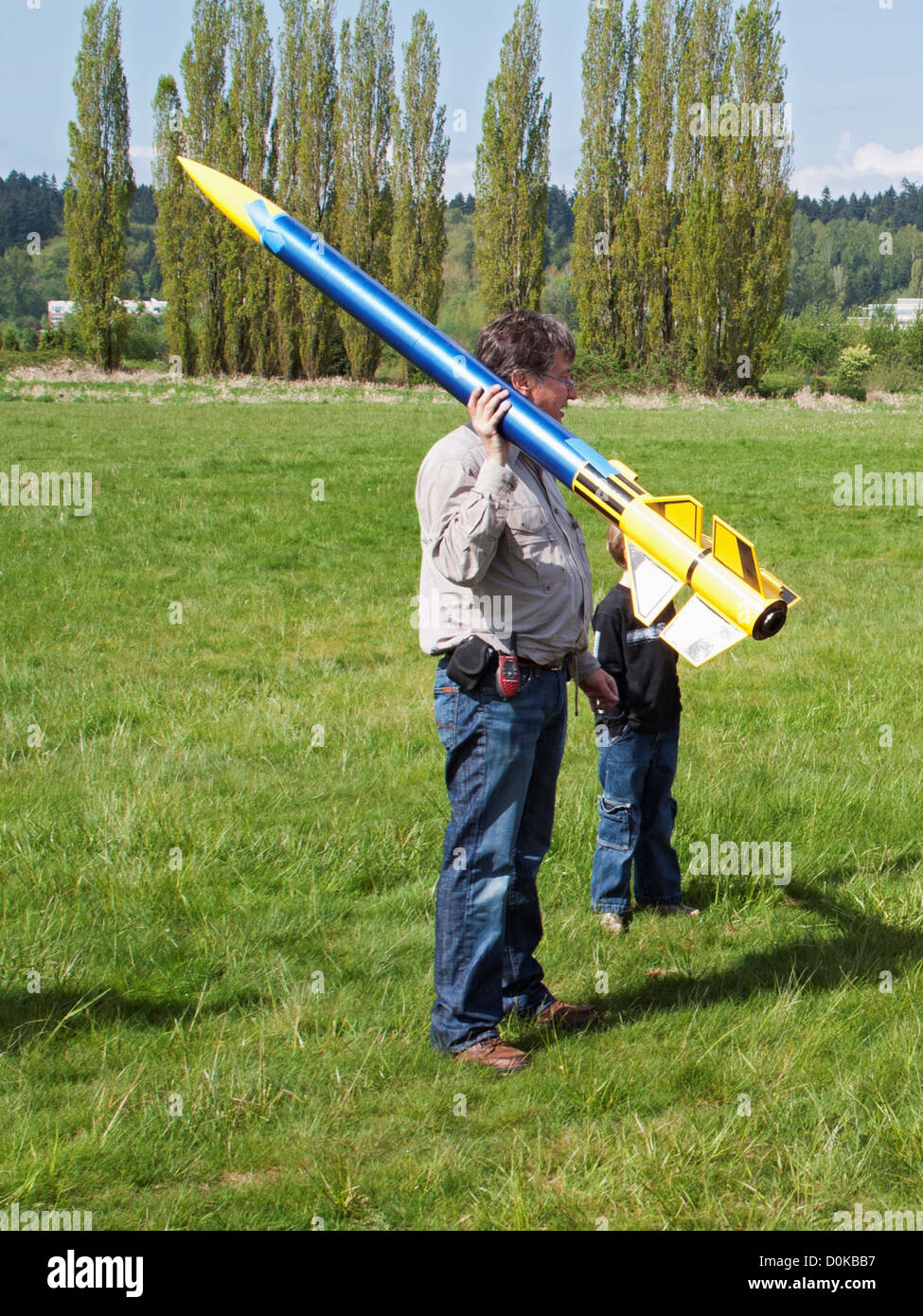 A man with a large model rocket at a rocketry launch event