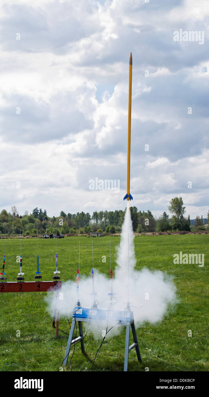 A tall yellow rocket, last in a row, launches from a