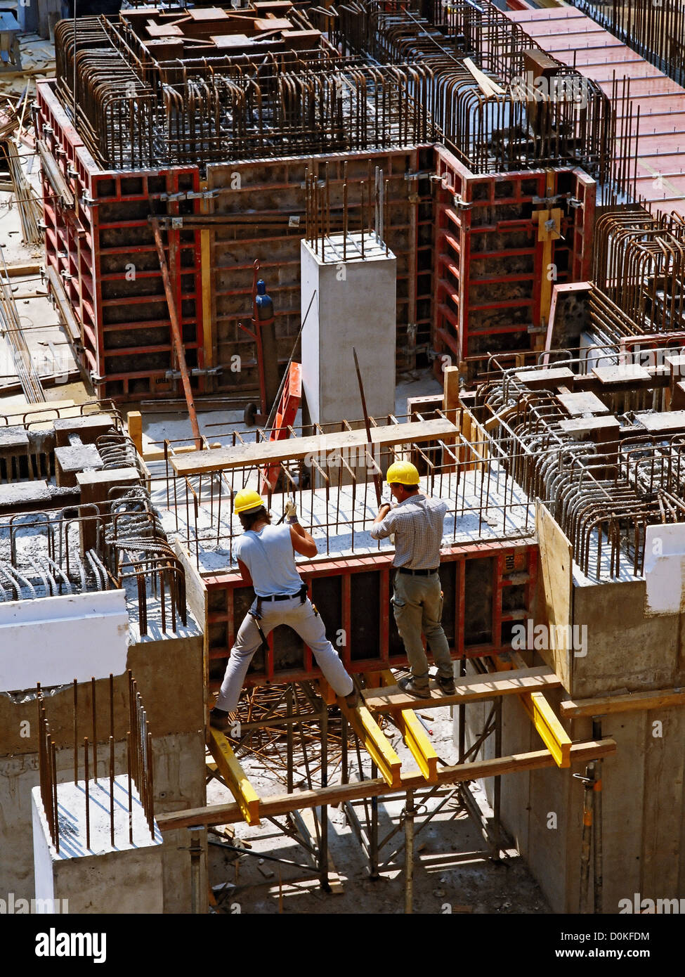 Workers building a steel-reinforced concrete structure. - Stock Image