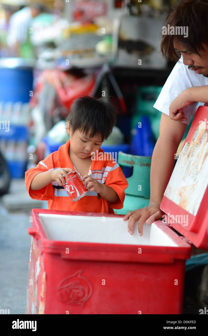 A young Thai boy takes a can of Coke from a cooler. - Stock Image