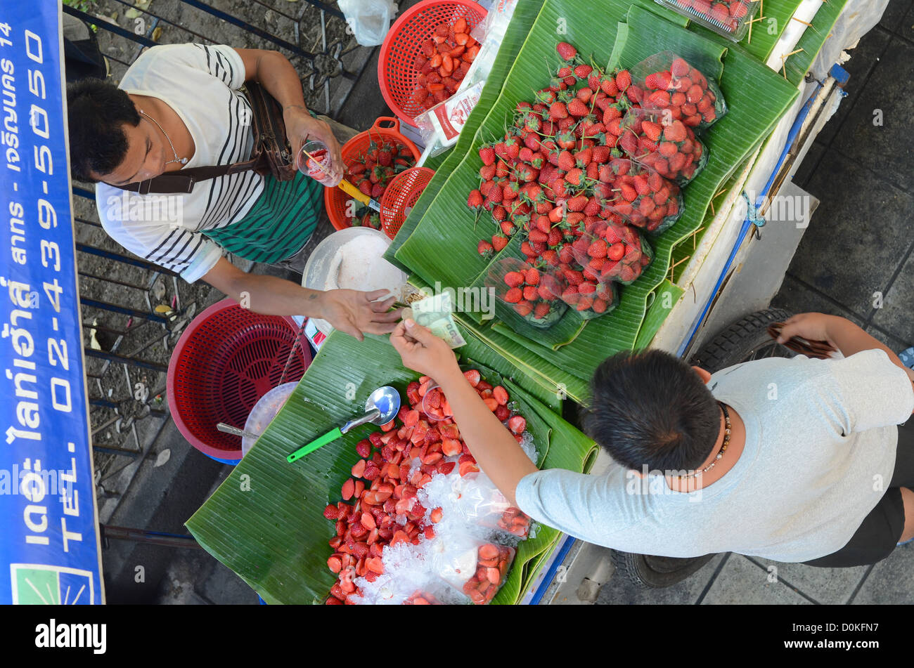 A shopper buying strawberries at Chatuchak market in Bangkok, Thailand. - Stock Image