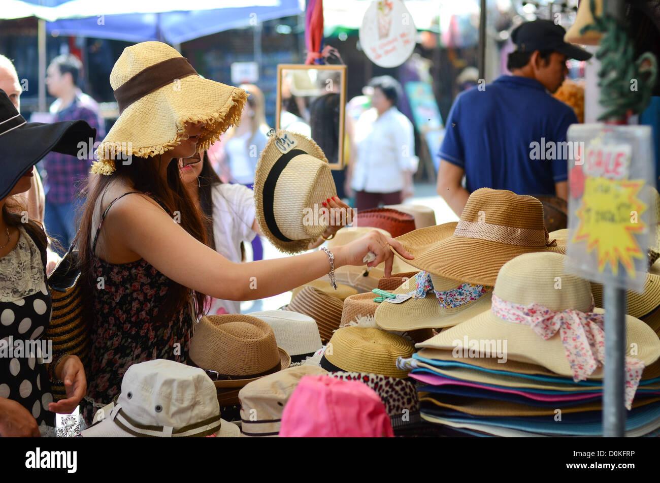 A woman looking at hats at Chatuchak market in Bangkok, Thailand. - Stock Image