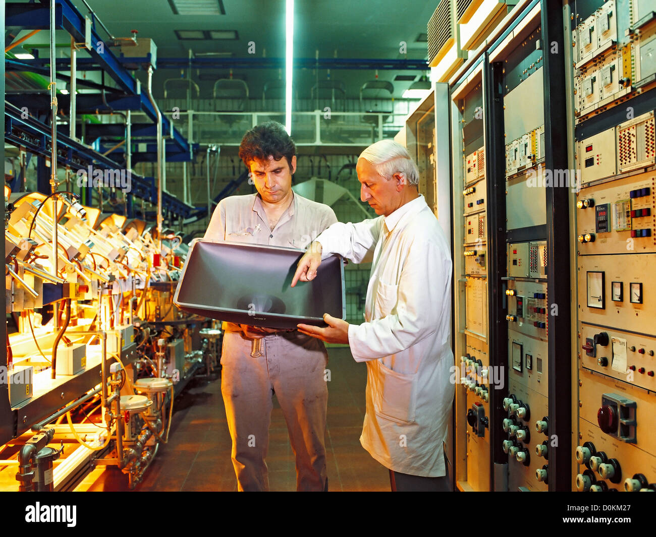 Technicians discussing manufacturing issues at a glass manufacturing plant. - Stock Image