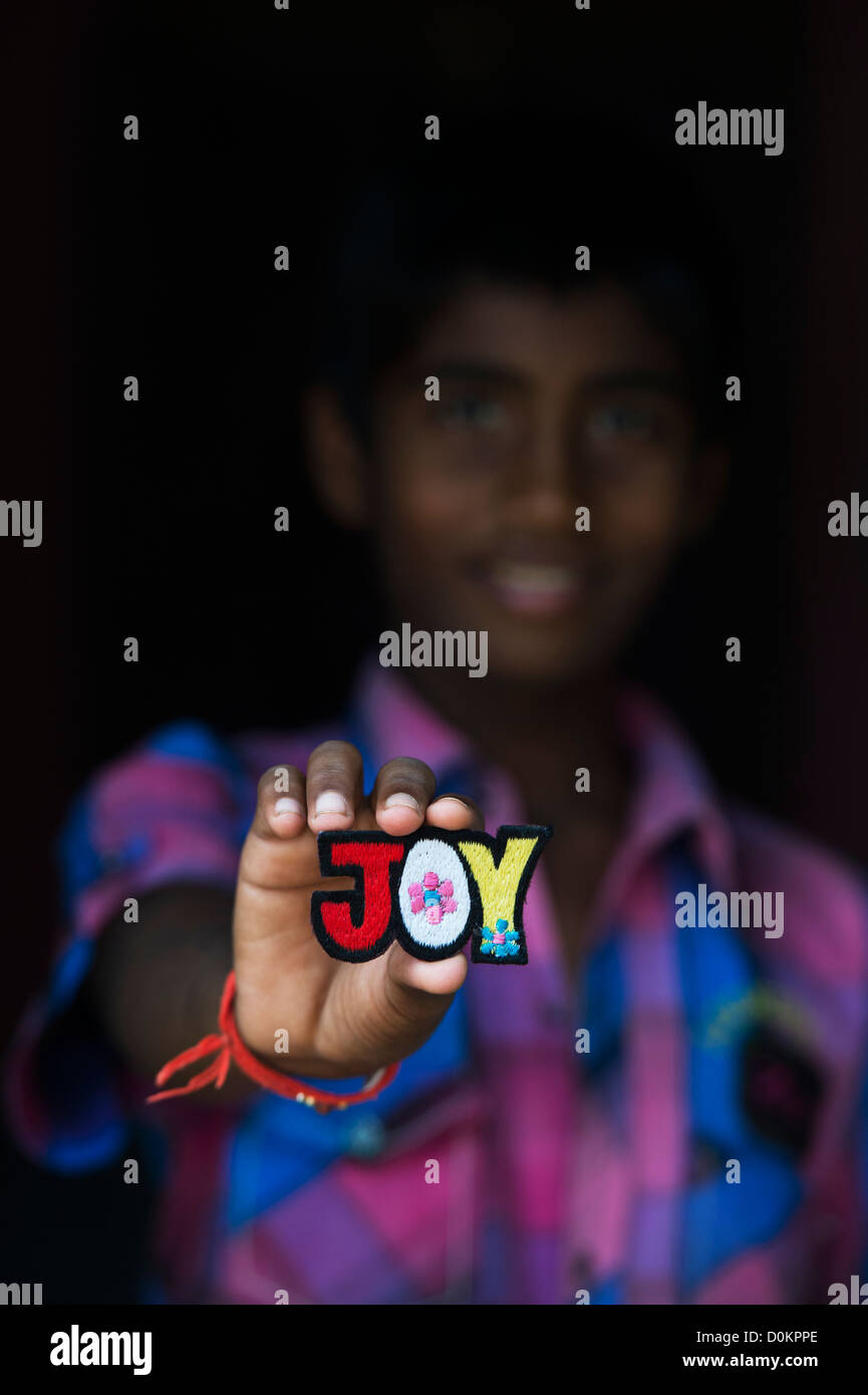 Smiling Indian boy holding a JOY multicoloured embroidery patch - Stock Image
