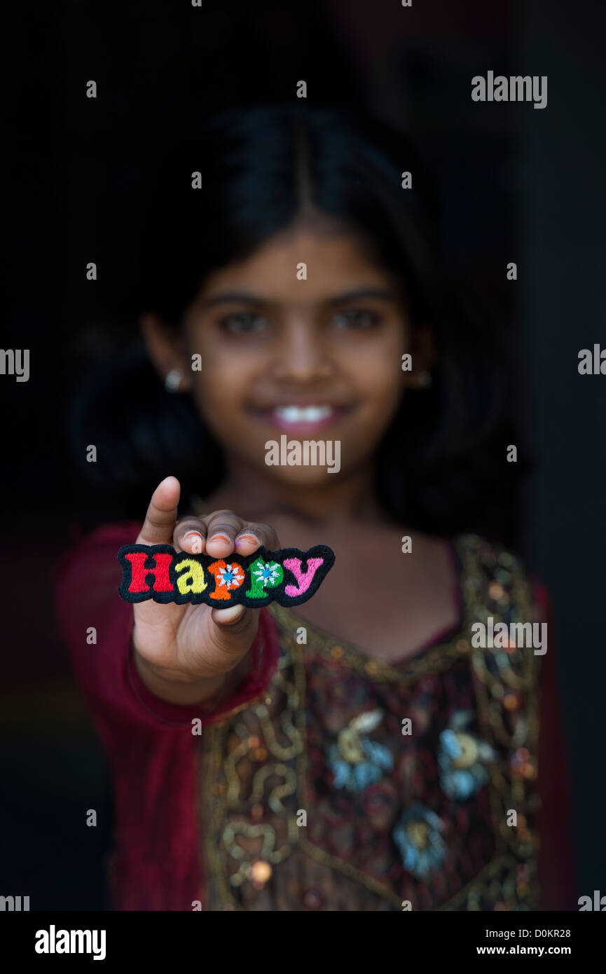 Smiling Indian girl holding a HAPPY multicoloured embroidery patch - Stock Image