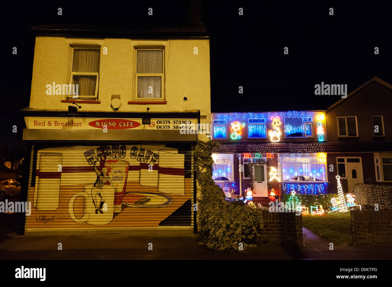 Over the top and tacky Christmas decorations on a residential house next to a cafe in West Thurrock in Essex. - Stock Image