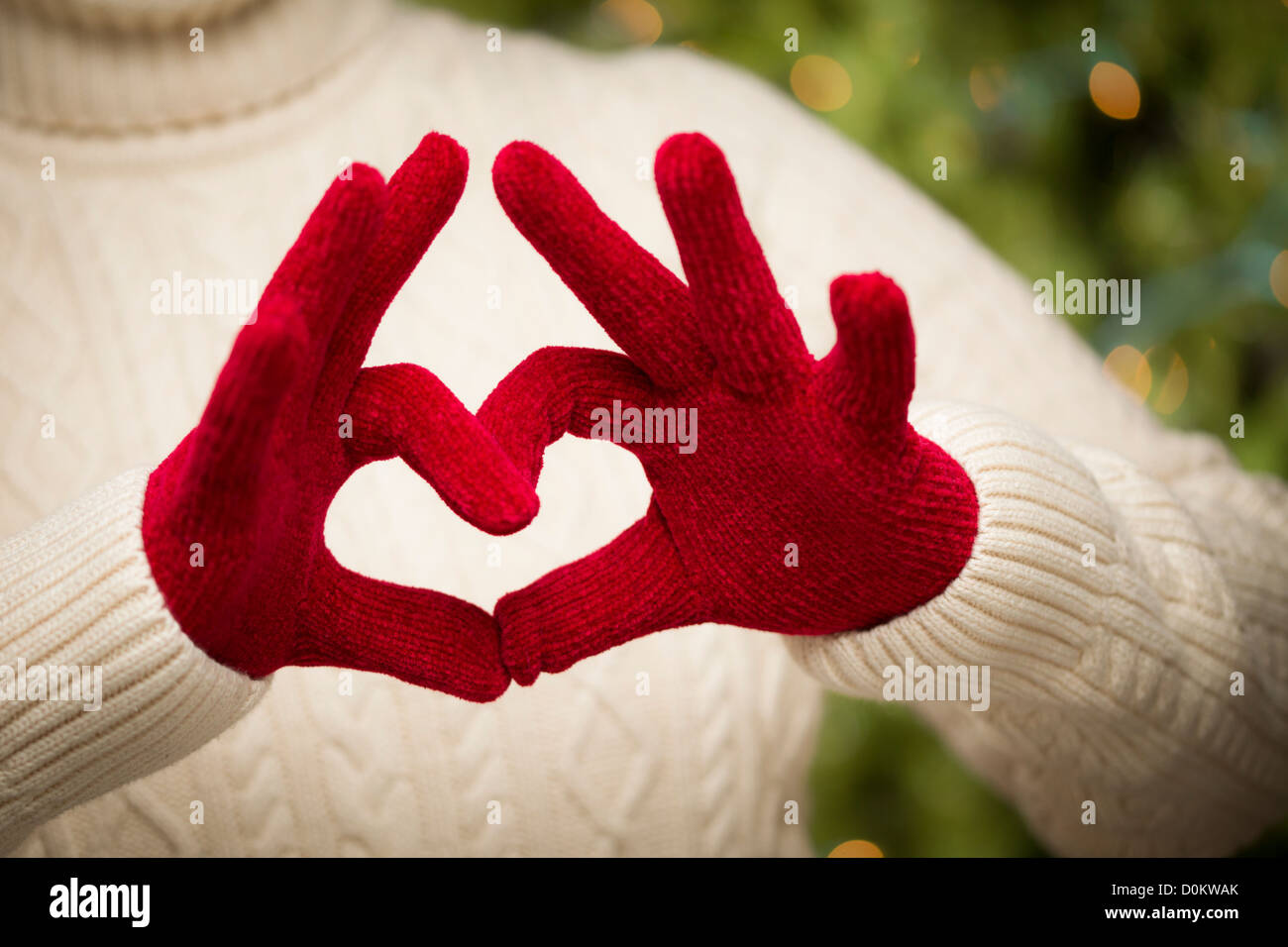 Woman in Sweater with Seasonal Red Mittens Holding Out a Heart Sign with Her Hands. - Stock Image