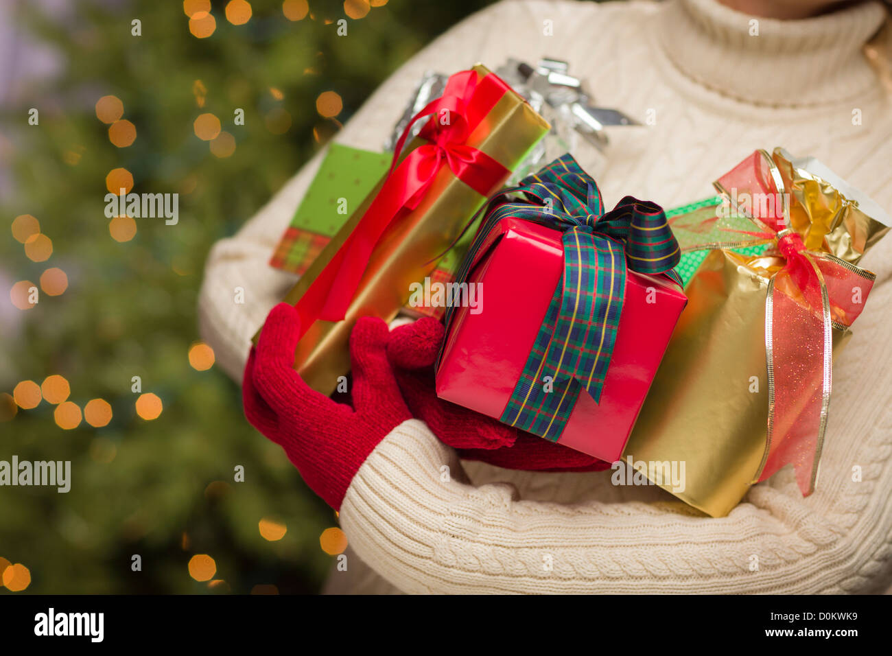 Woman Wearing A Sweater and Red Mittens Against an Abstract Green and Golden Background Holding Christmas Gifts - Stock Image