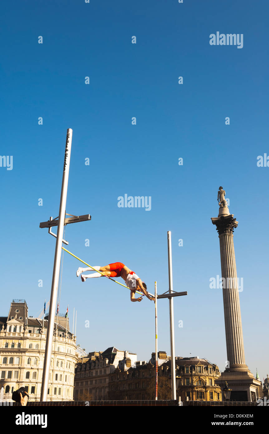 Pole vault in Trafalgar Square as part of a celebration of Dutch culture during the Holland House Festival. - Stock Image