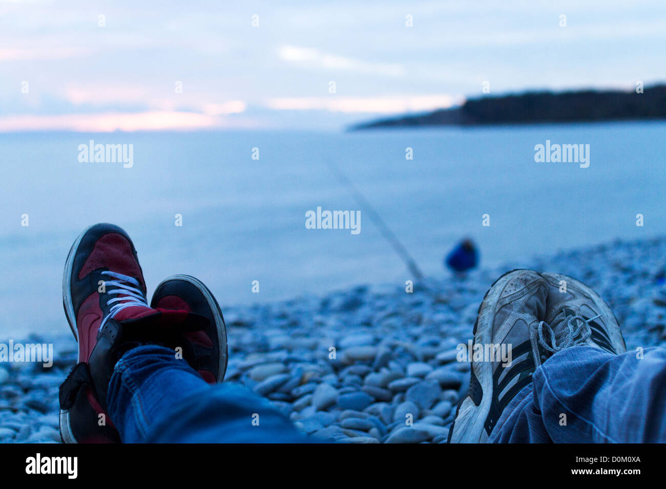 Two pairs of feet and shoes facing out to sea on the beach at sunset on Barry Island. Stock Photo