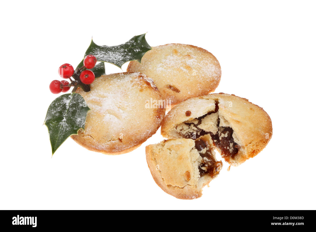 Group of mince pies dusted with icing sugar and decorated with a holly sprig isolated against white - Stock Image