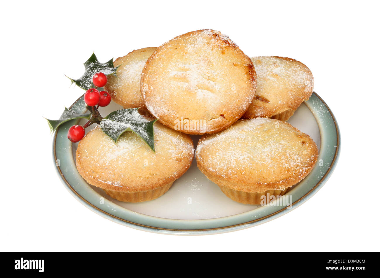 Mince pies on a plate dusted with icing sugar and decorated with holly isolated against white - Stock Image