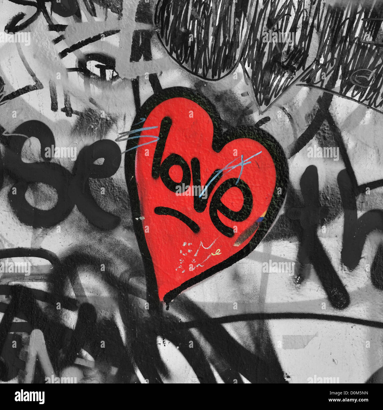 Red painted love heart on graffiti covered black and white wall background. Selective saturation. - Stock Image