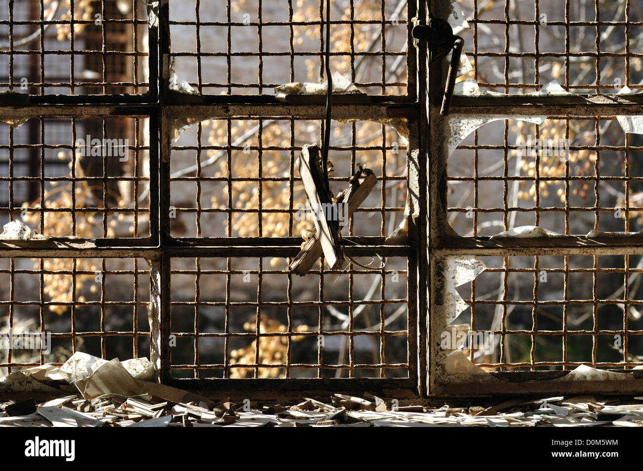 Broken glass window and rusty wire mesh background in abandoned warehouse. - Stock Image