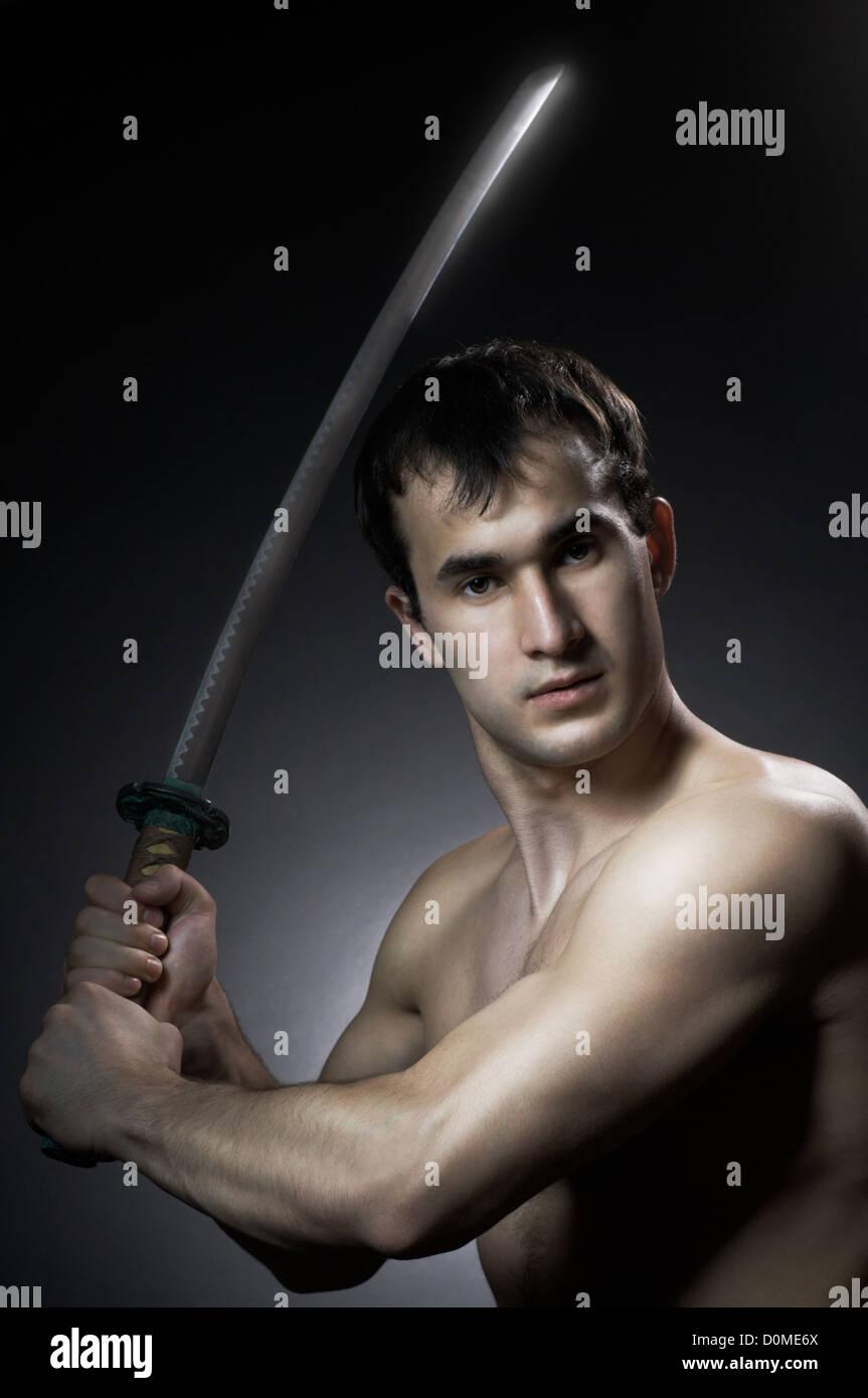 man training with blade on black background - Stock Image