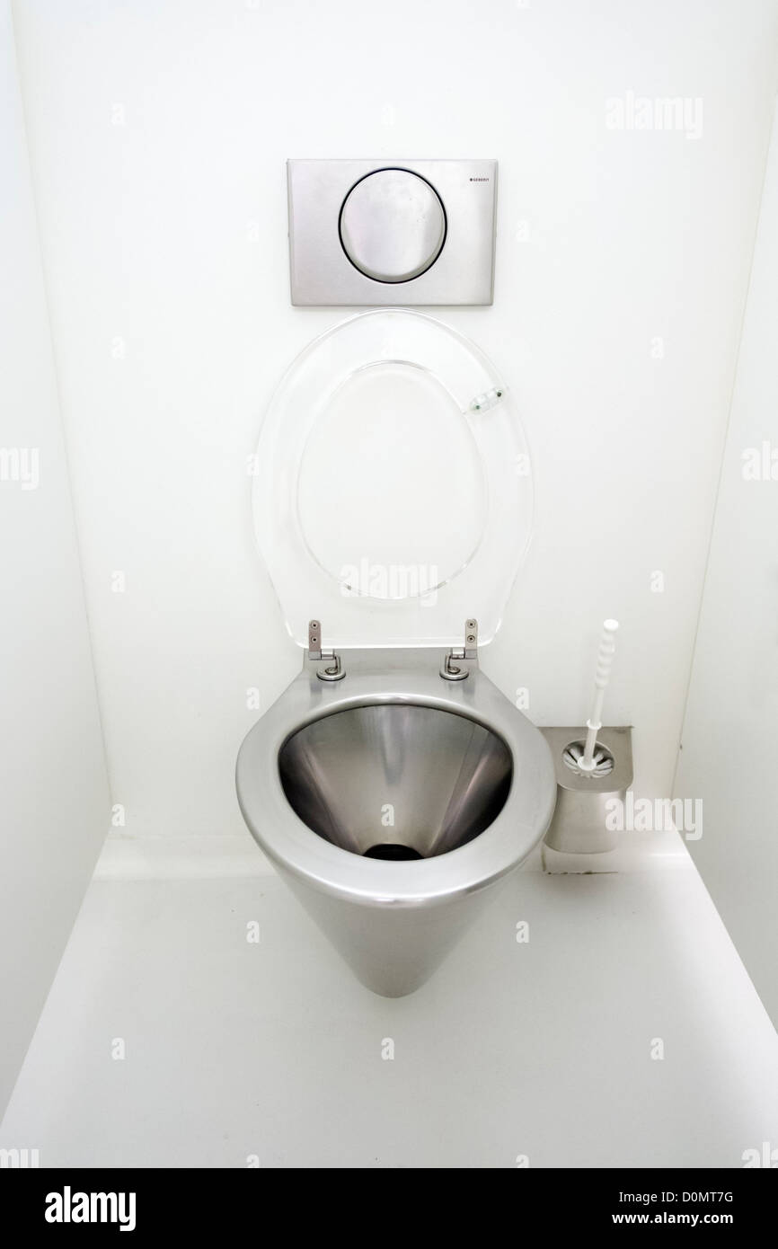 Modern stainless steel toilet bowl and fittings in lavatory cubicle - Stock Image