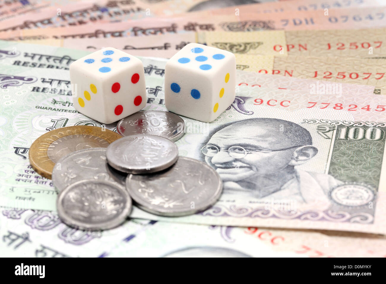 Dices and rupee coins on Indian rupee notes - Stock Image