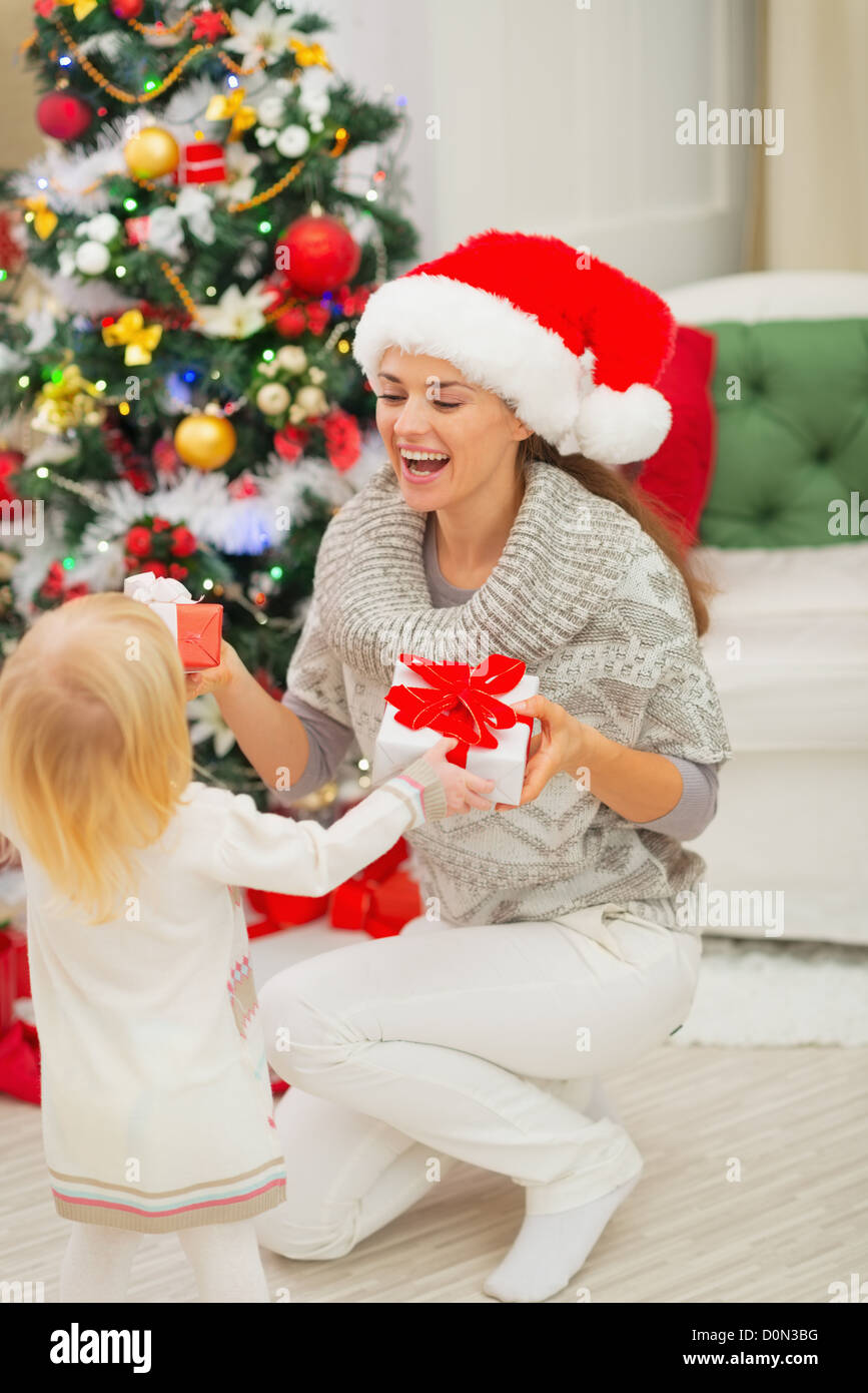 Mom and baby girl changing Christmas presents Stock Photo: 52094772 ...