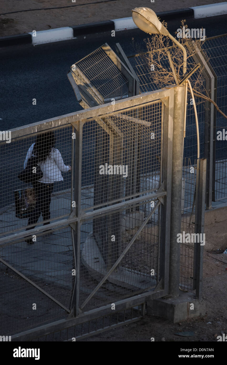 A woman carrying a shopping bag passing in front of a closed gate Stock Photo