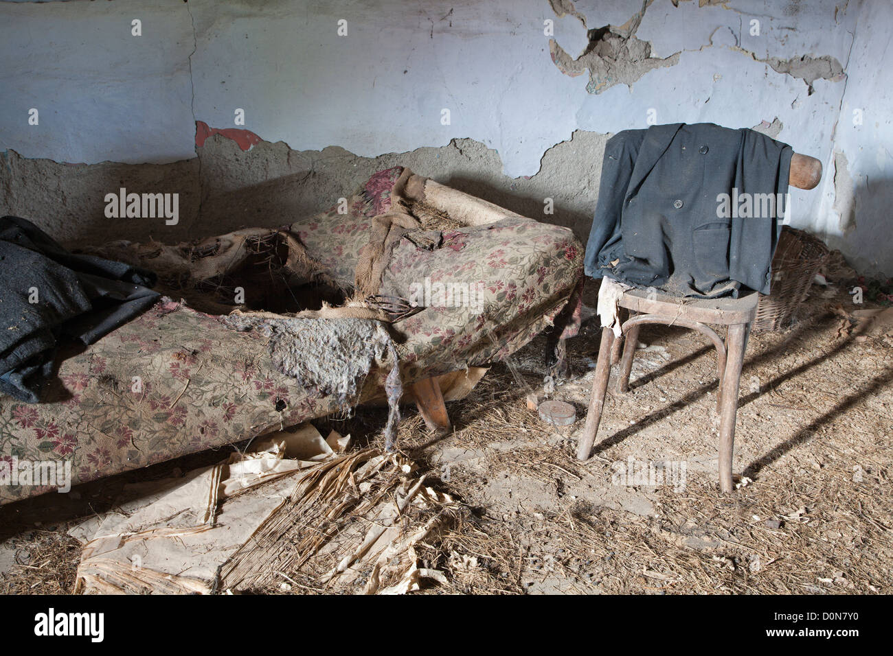 old chair and bed in ruined house - Stock Image