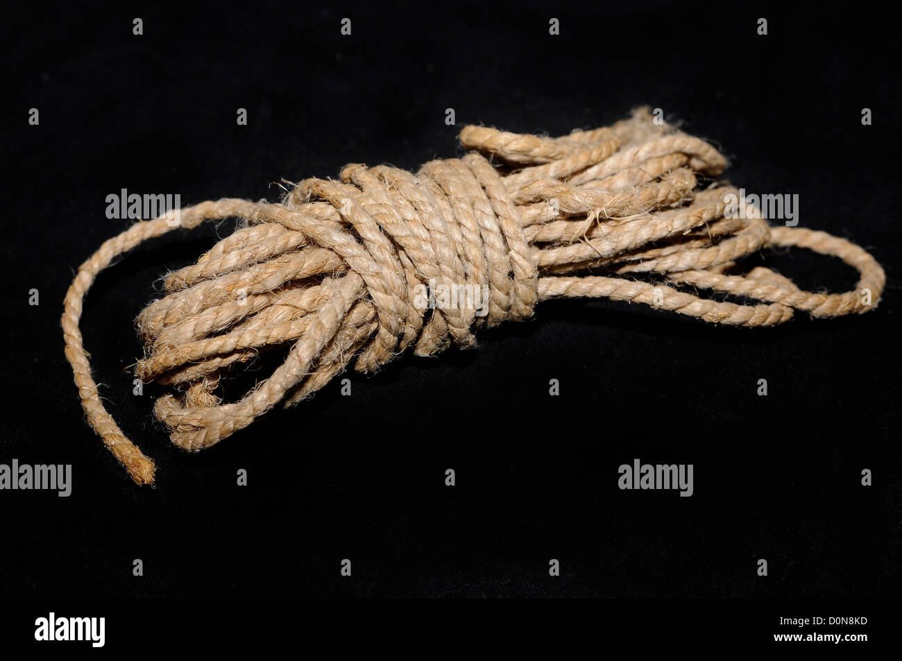 hemp rope,rope, all tied, case closed, ball of string on a black background - Stock Image